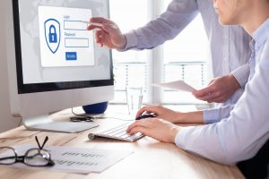 secure login on computer with two business people